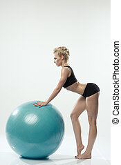 Beautiful sporty woman doing stretching exercise with ball