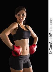 Beautiful sporty woman posing wearing boxing gloves looking...