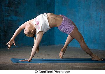 Beautiful sporty young woman Doing Camatkarasana posture