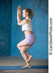 Beautiful sporty young woman Doing Garudasana posture