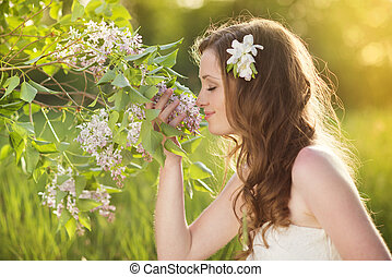 Beautiful spring girl with flowers on the meadow