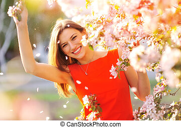 Beautiful Spring woman with blossoming flowers on trees in garden