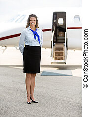 Beautiful Stewardess Standing Against Private Jet - Full...