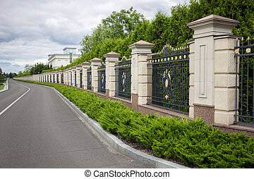 Beautiful stone fence with forged metal gates painted with...