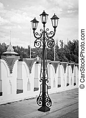 street lamp on an old stone bridge black and white
