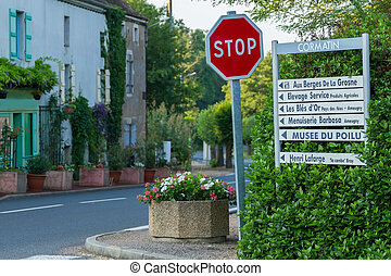 Beautiful street with signs for tourists with flowers of Burgundy region in Cormatin, France