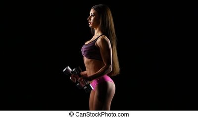 Beautiful strong woman exercises with dumbbells on black