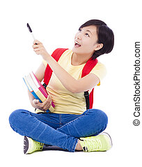 beautiful student asian girl holding pen and sitting on floor