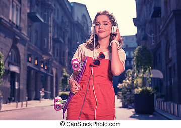 Beautiful student feeling relaxed while walking the street listening to music