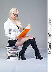 Beautiful student is sitting on the books