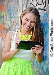 Beautiful stylish fashion blond woman reading message on tablet pc at graffiti wall