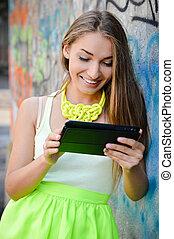 Beautiful stylish fashion woman reading message on tablet pc at graffiti wall