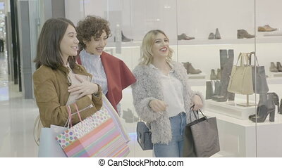 Beautiful stylish fashionable young girls at the mall wearing expensive clothes and getting excited and having reactions to sales they see in the window store