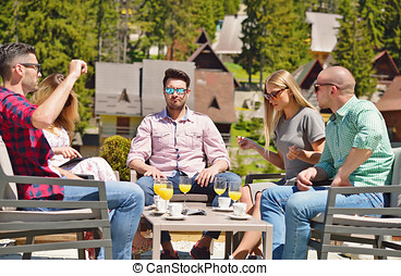 Beautiful stylish friends are using a digital tablet, drinking coffee and smiling while resting in the park