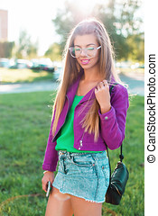 Beautiful stylish girl in a bright colorful fashionable clothes and sunglasses on a sunny day.