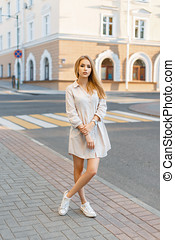 Beautiful stylish girl in a dress and sneakers standing near the building on a sunny summer day