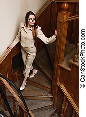 Beautiful stylish lady in suit wallks downstairs
