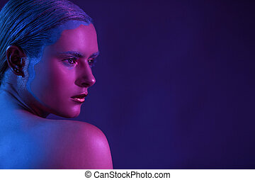Beautiful stylish model with half face on a purple background.