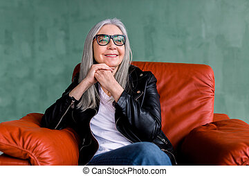 Beautiful stylish senior woman with long straight gray hair, wearing eyeglasses and black leather jacket, sitting in comfortable sofr red armchair on green background and dreamly looking aside