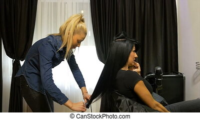 Beautiful stylish woman getting her hair done at beauty salon while talking on the mobile phone