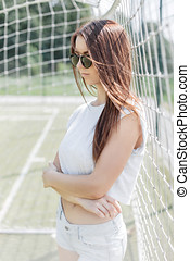 Beautiful stylish woman in summer dress standing on a football field near the grid