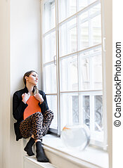 Beautiful stylish young girl with book on the windowsill dreamily looks up