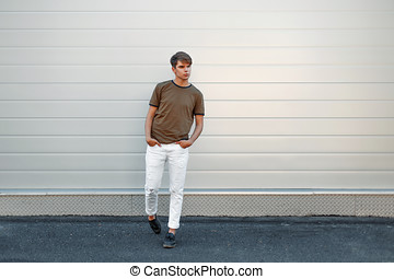 Beautiful stylish young man in a fashion T-shirt and white pants with black leather pants near the gray metal wall