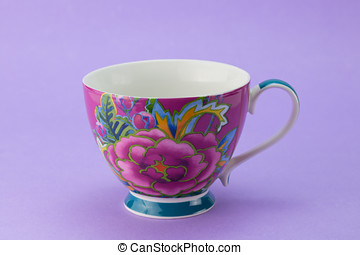 Beautiful stylized empty rose tea cup isolated on lilac background