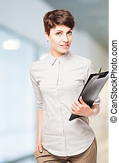 beautiful successful woman office worker with a folder in his hands posing in the office
