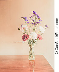 Beautiful summer flowers in vases on wooden background