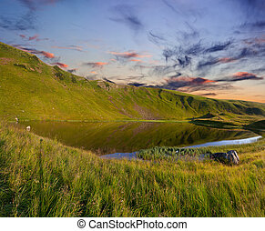 Beautiful summer landscape in the mountains with a lake. Sunrise