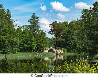 Beautiful summer landscape with an old bridge over the pond in the Park