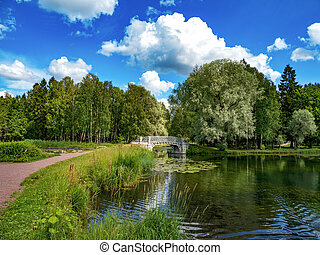 Beautiful summer landscape with an old park and a bridge on the lake. Gatchina