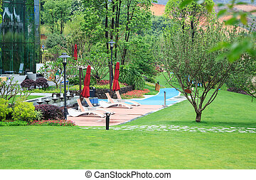 Beautiful summer park with green lawns and deck chairs