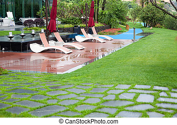 Beautiful summer park with green lawns and flower beds after rain
