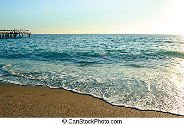 Beautiful Summer Seascape with Waves of Blue Sea and Sand Beach in Sun Light. Travel and Vacation Concept.