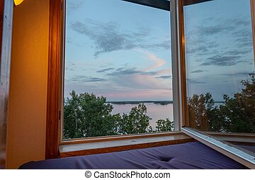 Beautiful summer sundown view from open window. Top of green trees on lake and cloudy sky background.