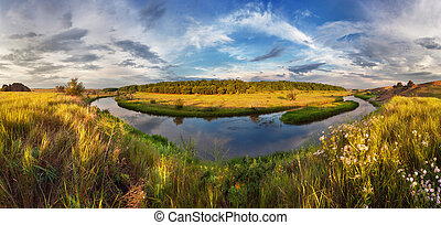 Beautiful summer sunset at the river with blue sky, clouds, yell