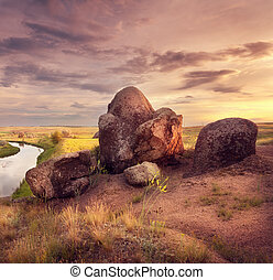 Beautiful summer sunset at the river with old stones
