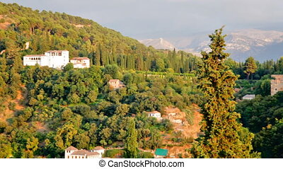 Beautiful summer view on Alhambra castle up the green hill under cloudy sky