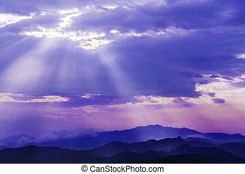 sun light through cloud sky over mountain