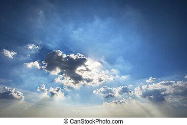 beautiful sun light through dramatic cloud against blue sky