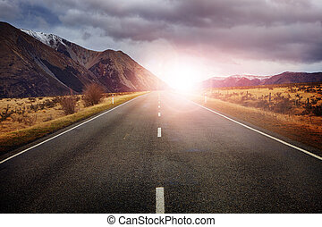 beautiful sun rising sky with asphalt highways road against snow mountain arthur's pass scenery background in new zealand