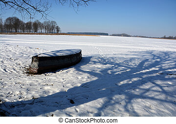 sunny winter lake landscape with old boat and tree shadow