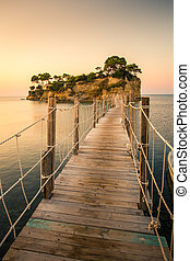 Beautiful sunrise at the famous Cameo island. A beautiful small island with wooden bridge and turquoise water. Zakynthos Greece. In summer.