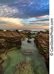 sunrise at the Playa de las Catedrales Beach in Galicia in northern Spain with tidal pools in the foreground