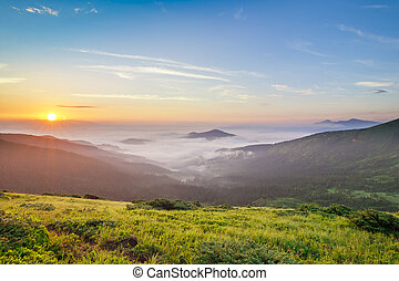 Beautiful sunrise in mountains with white fog below