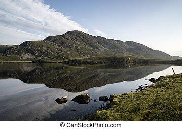 Beautiful sunrise mountain landscape reflected in calm lake