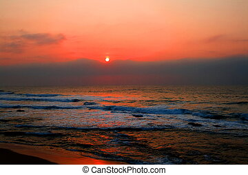 beautiful sunrise on indian ocean with red ligts reflecting on the sea surface, taken at Umhlanga beach in South Africa
