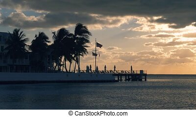 Beautiful sunrise on Key West, Florida, USA. With palms and resorts on background. Sunset over the sea at Key West, Florida. America flag waving in the wind, key west, Florida